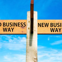 Wooden signpost with two opposite arrows over clear blue sky Old Business Way and New Business Way Business change conceptual image